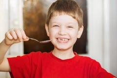 Glücklicher kleiner lächelnder Kleinkindgrifflöffel stockfotos