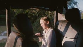 Glücklicher kleiner lächelnder Mädchenkindertourist, der Nationalparkexkursionsreise innerhalb des Safariauto-LKWs an einem sonni stock footage