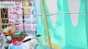 Glücklicher kleiner netter Junge fährt auf Karussell mit Autos stock video