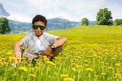 Glücklicher kleiner schwarzer sitzender Junge in der Sonnenbrille Stockfotos
