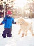 Glücklicher Kleinkindjunge, der draußen mit weißem Hund in Wintertag läuft und spielt Lizenzfreies Stockbild