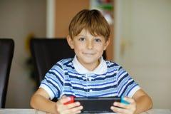 Glücklicher Kleinkindjunge, der mit Gamecontroller spielt Kinderspiel mit Freunden zu Hause über Internet-Konsole lizenzfreies stockfoto
