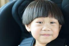 Glücklicher Kleinkindjunge des Porträts, der im Autositz sitzt stockbild