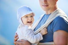 Glücklicher Kleinkindjunge im Riemen, tragender Sohn des Vaters lizenzfreie stockbilder