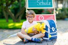Glücklicher Kleinkindjunge mit den Gläsern, die durch Schreibtisch und Rucksack oder Schultasche sitzen Stockfotos