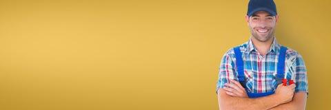 Glücklicher Klempnermann, der einen Schlüssel gegen gelben Hintergrund hält Stockfotos