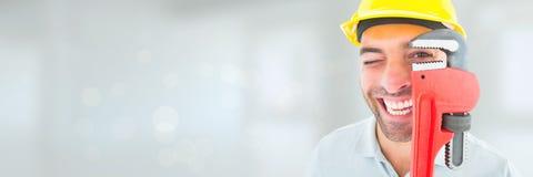 Glücklicher Klempnermann, der einen Schlüssel gegen weißen Hintergrund mit Aufflackern hält Lizenzfreies Stockbild