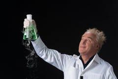Glücklicher Kliniker studiert im Labor und oben halten Flasche Stockfotografie