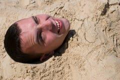Glücklicher Kopf im Sand Lizenzfreie Stockfotos