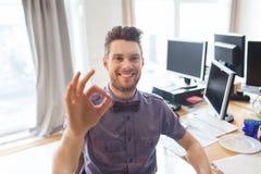 Glücklicher kreativer männlicher Büroangestellter, der okayzeichen zeigt Stockbild