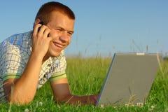 Glücklicher Kursteilnehmer, der mit Laptop auf grüner Wiese arbeitet lizenzfreie stockfotos