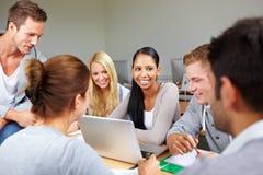 Glücklicher Kursteilnehmer mit Gleichen in der Hochschule Lizenzfreie Stockbilder