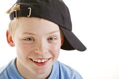 Glücklicher lächelnder 12 Einjahresjunge mit einer Schutzkappe getrennt Stockfotos