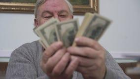 Glücklicher lächelnder alter Mann, der oben die Dollar nah zählt Positiver Reicher demonstriert sein Geld lustiger Großvater stock footage