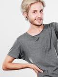 Glücklicher lächelnder blonder Mann im grauen T-Shirt Lizenzfreie Stockfotos