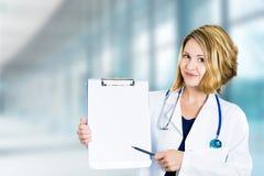 Glücklicher lächelnder Doktor mit dem Klemmbrett, das in der Krankenhaushalle steht Stockfotos