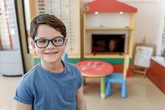 Glücklicher lächelnder flüchtiger Blick des Kindes in den Schauspielen Lizenzfreies Stockbild