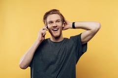Glücklicher lächelnder froher Guy Talking auf Smartphone stockfotografie