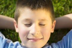 Glücklicher lächelnder froher schöner Junge, der den Spaß im Freien und das Lügen hat Stockfotografie