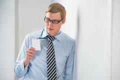 Glücklicher lächelnder Geschäftsmann in den Gläsern, die leeren Ausweis zeigen Stockbilder