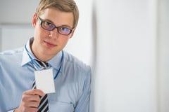 Glücklicher lächelnder Geschäftsmann, der leeren Ausweis zeigt stockbild