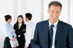 Glücklicher lächelnder Geschäftsmann mit Kollegen Stockfotos