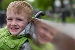 Glücklicher lächelnder hübscher blonder Junge, der auf einer Bank sitzt Lizenzfreies Stockbild