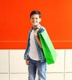 Glücklicher lächelnder Jugendlicher des kleinen Jungen des Porträts mit Einkaufstasche in der Stadt Stockfoto