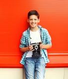 Glücklicher lächelnder Jugendlicher des kleinen Jungen mit Retro- Weinlesekamera Stockfoto