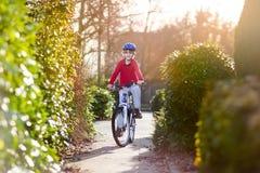 Glücklicher lächelnder Jugendlichjunge, der sein Fahrrad auf Sonnenuntergang reitet Stockbilder