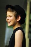 Glücklicher lächelnder Junge in einem schwarzen Hut Stockfotos