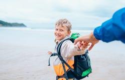 Glücklicher lächelnder Junge hält seinen Vater an Hand und läuft zur Brandung Lizenzfreie Stockbilder