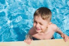 Glücklicher lächelnder Junge am Pool stockbild