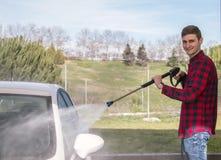 Glücklicher lächelnder junger Mann, der sein Auto an der Druckwaschanlage wäscht Lizenzfreies Stockfoto