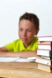 Glücklicher lächelnder kaukasischer Junge, der am Tisch sitzt Lizenzfreie Stockfotos