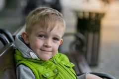 Glücklicher lächelnder kleiner blonder Junge, der auf einer Bank sitzt Stockbilder