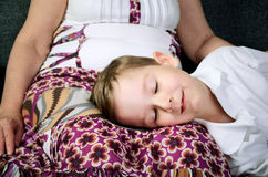 Glücklicher lächelnder kleiner Junge, der nahe seiner Großmutter schläft Stockbilder