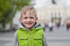 Glücklicher lächelnder kleiner stilvoller blonder Junge, der Kamera betrachtet Lizenzfreies Stockbild