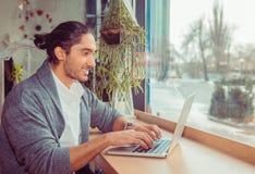 Glücklicher lächelnder Mann, der am Laptop schreibt lizenzfreie stockbilder