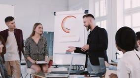 Glücklicher lächelnder Mitte gealterter Geschäftstrainer, der mit Team am modernen hellen Büroarbeitsplatz spricht Zeitlupe ROTES stock video