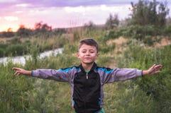 Glücklicher lächelnder netter Junge mit Augen schloss das Genießen auf einem schönen Sommernaturhintergrund lizenzfreie stockfotos