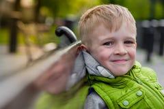 Glücklicher lächelnder schöner blonder Junge, der auf einer Bank sich entspannt Stockbilder