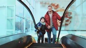 Glücklicher lächelnder Vater und sein aufgeregter Sohn an der Rolltreppe stock video