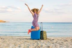 Glücklicher lachender Frauentourist mit den Koffern, die nahe dem Meer stehen Reise- und Sommerferienkonzepte Stockbilder