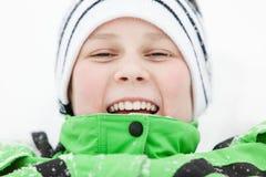 Glücklicher lachender Junge, der im Winterschnee liegt Stockfotos