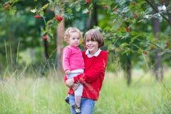 Glücklicher lachender Junge mit seinem kleinen Schwesterchen im Park Lizenzfreie Stockbilder