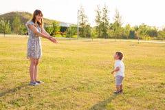 Glücklicher lachender kleiner Junge, der in der Natur mit Mutter spielt Stockfotografie