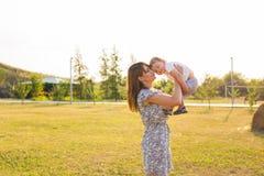 Glücklicher lachender kleiner Junge, der in der Natur mit Mutter spielt Stockfoto