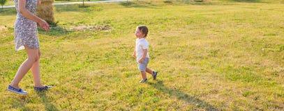 Glücklicher lachender kleiner Junge, der in der Natur mit Mutter spielt Lizenzfreie Stockfotografie