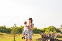 Glücklicher lachender kleiner Junge, der in der Natur mit Mutter spielt Stockbild